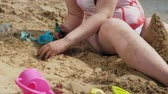 uczennica : Girl builds a sand castle on the river bank Wideo