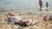 brisa : Young woman lying on the beach Stock Footage