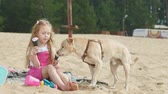 lody : Girl eats ice cream and feeds the dog outdoors.