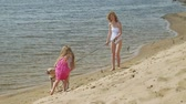 plavky : Mother and daughter run along the river bank with a dog. Sunny summer day. Family holiday