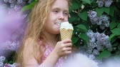 ワッフル : Little girl eats ice cream outdoors. Summer 動画素材
