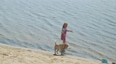 przyjaźń : Little girl walks on the beach by the river with a dog Wideo