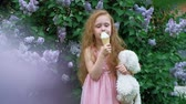 eats : Little girl eats ice cream outdoors. Summer Stock Footage