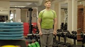 hombres : A overweight man lifts an ez barbell while standing at the gym. Exercise for biceps. Fitness. Healthy lifestyle.