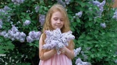 cheiro : A little girl outdoors in a park or garden holds lilac flowers. Lilac bushes in the background. Summer, park