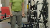 sovrappeso : A overweight man lifts an ez barbell while standing at the gym. Exercise for biceps. Fitness. Healthy lifestyle.