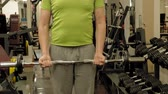 бицепс : A overweight man lifts an ez barbell while standing at the gym. Exercise for biceps. Fitness. Healthy lifestyle.