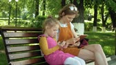 sní : Mom and daughter use gadgets in the open air. Summer