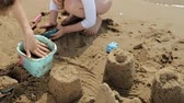 výhonky : Mom and daughter are playing on the beach, building a sand castle. Summer sunny day. vacation. Aerial shooting
