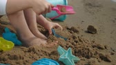 traje de bano : Girl child plays with sand on the beach using molds figurines. Sunny summer day. vacation