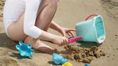 próximo : Girl child plays with sand on the beach using molds figurines. Sunny summer day. vacation