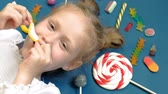 marmelat : Cheerful little girl lies on a blue background with sweets. Closeup portrait Stok Video