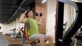 weights : A man doing a bench press with dumbbells sitting with a straight grip in a fitness studio Stock Footage