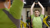 поднимать : Man doing bench press with dumbbells in fitness studio
