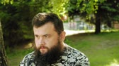 independent : mature bearded man depicts emotions outdoors. summer Stock Footage