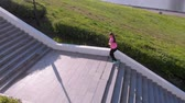 camiseta : A young girl runs up the stairs, sports. Aerial shooting