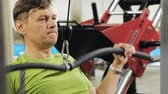 верхний : The overweight man shares the upper block in the gym. Fitness. Healthy lifestyle. Стоковые видеозаписи