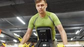 бицепс : Man works out at the gym on simulators. Sport .Healthy lifestyle Стоковые видеозаписи