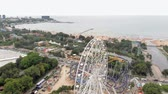 Amusement park by the sea. View of the ferris wheel and the water park with a drone. Shooting from a height