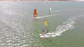 アクションショット : A man floats on a surf board with a sail. Aerial shot