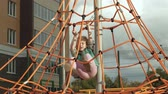 plac zabaw : A child climbs a rope horizontal bar in an outdoor playground Wideo