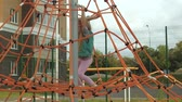 aire de jeux : A child climbs a rope horizontal bar in an outdoor playground Vidéos Libres De Droits