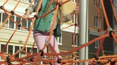 saamhorigheid : A child climbs a rope horizontal bar in an outdoor playground Stockvideo