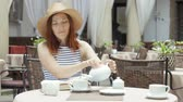jaro : beautiful young girl in outdoor cafe reading a book and drinking tea. phone. student. business woman Dostupné videozáznamy