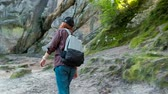 enjoying : Hiker woman hiking in forest, stops and looks around. Smiling happy active female during hike in forest