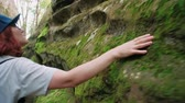 tentar : Girls touching with hands a big green stone covered with moss in the forest during walking