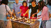 dagon : YANGON. MYANMAR - 03 JAN 2014: Women lighting oil lamps - a traditional ritual