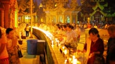 dagon : YANGON. MYANMAR - 03 JAN 2014: Set parishioners participate in an evening ritual lighting of fires in Shwedagon Pagoda Stock Footage