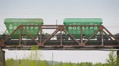 heavy : UltraHD video - Freight train moving along the bridge over the river Stock Footage