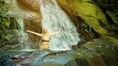 wet : Video UHD - Young woman bathing in a natural waterfall in the rainforest
