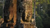 nagy : Two hand sculpted faces stare outward from a single stone religious monument at Bayon Temple. Siem Reap. Cambodia.