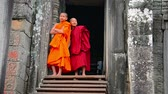 kazınmış : SIEM REAP. CAMBODIA - CIRCA DEC 2013: Two child monks in traditional robes are conscious of the camera as they stand in the doorway to Bayon Temple in Siem Reap. Cambodia. Stok Video