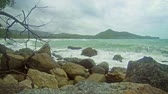 manzara : Video FullHD - Small. foamy waves wash over and around large boulders on a breezy. cloudy day at the beach in Thailand. Southeast Asia. Stok Video