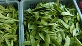 inexpensive : Video 1080p - Heaps of Chinese snow peas displayed in blue. plastic baskets. alongside eggplants at a local public market in Southeast Asia.
