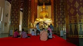 Аюттхая : AYUTHAYA. THAILAND - CIRCA FEB 2015: Buddhist worshippers sit on a red carpet before an enormous. gilded Buddha statue to pray at Wat Na Phramen in Ayutthaya. Thailand.