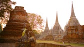 Аюттхая : Video 1080p  Tourists. strolling around a courtyard near an ancient temple ruin amongst the old stone stupas and sculptures at Wat Phra Si Sanphet in Thailand