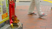 corner : HONG KONG. CHINA - CIRCA JAN 2015: Pedestrian traffic walking by a little Buddhist shrine along the sidewalk in downtown Hong Kong.