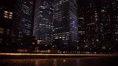 major city : UltraHD video  Beautifully lit. modern highrise buildings along a concrete boat quay in a major. metropolitan city at night.