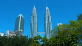 KUALA LUMPUR. MALAYSIA  CIRCA FEB 2015: The iconic Petronas Twin Towers. standing against a clear blue sky. as seen from Kuala Lumpur City Centre Park. in Malaysias capital city.