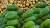 flavour : Video 1080p - Small. green mangoes. harvested early for their sour flavor. and sweet lanzones fruit. piled high for sale at an outdoor. public market in Asia.