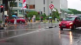 осадки : SINGAPORE - CIRCA AUG 2015: Pedestrian and vehicle traffic at a downtown intersection in Singapore on a rainy afternoon. Стоковые видеозаписи