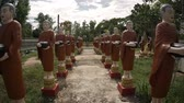 bo : Dozens of identical monk statues with brown robes. standing on pedestals flanking an ancient walkway at Wat Bo temple territory in Siem Reap. Cambodia.