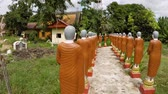 bo : Many identical monk statues. standing on a golden pedestals. painted with brown robes and gray hair. outside Wat Bo Temple in Siem Reap. Cambodia. Stok Video