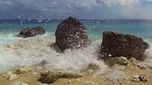 hrubý : Gentle waves splash and wash over pitted boulders of a tropical beach with a beautiful. flat horizon in the background. with Sound. Video 1080p