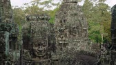 esculpida : Ancient. lichen covered  faces. carved from enormous blocks of stone stand among the trees at Bayon Temple. Cambodia. with jungle sounds in the background. Video UltraHD