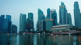 fullerton : SINGAPORE - CIRCA AUG 2015: Horizontal panning of Marina bay waters and downtown with modern glass skyscrapers and Singaporean icon Merlion in early morning light.